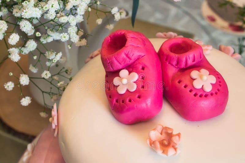 Baby showerkaka med små rosa marsipanbyten för en flicka och en blom- ordning royaltyfri fotografi