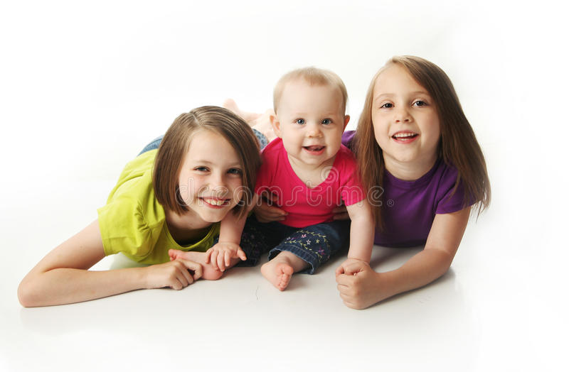 Baby sister and two big sisters stock images