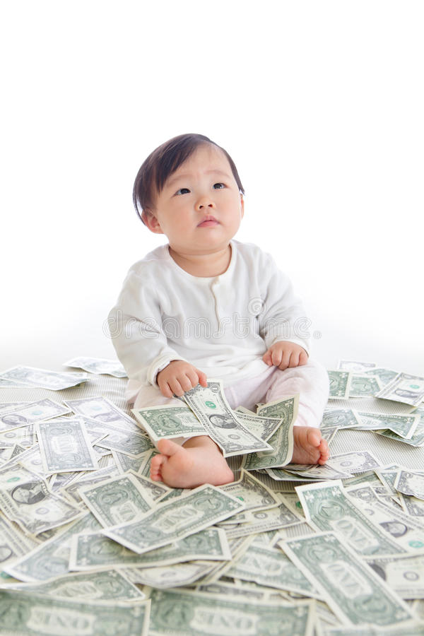Baby sit on floor with many money stock image