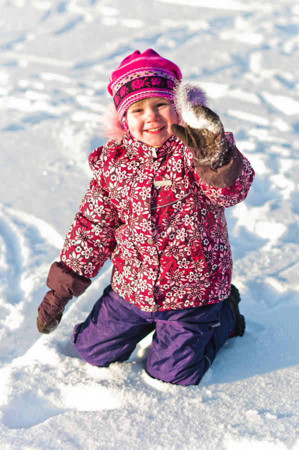 Baby sits on snow and smile