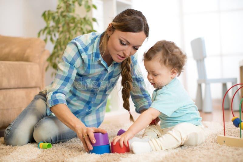 Baby-sitter com a criança que joga no berçário imagem de stock