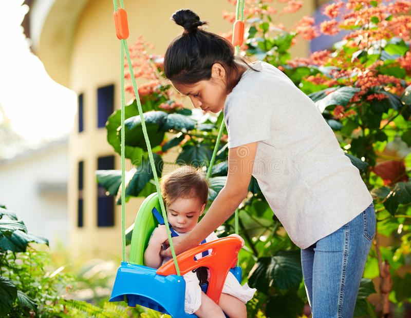 Baby sitter take care of child. On house garden background stock photography
