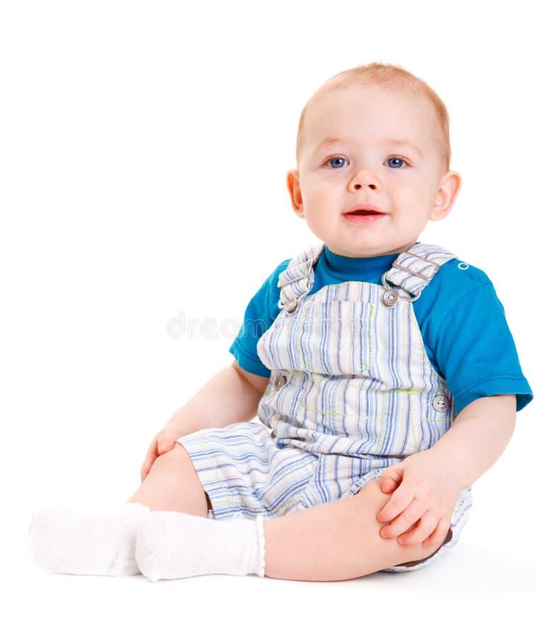 Baby sitting. Smiley baby boy sitting, isolated stock image