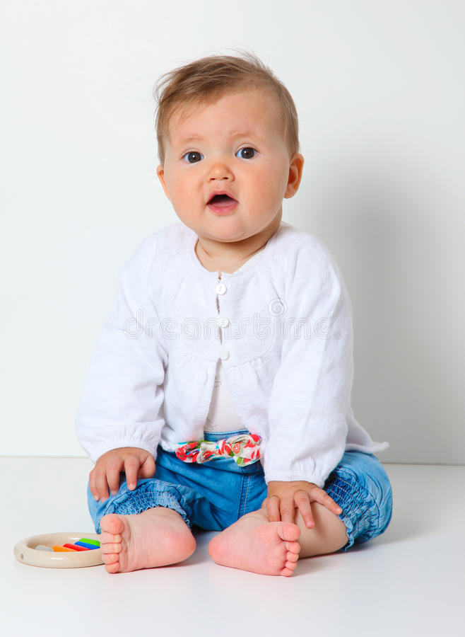 Baby sitting. 7 month old baby sitting with toy dressed in jeans and jumper stock photos