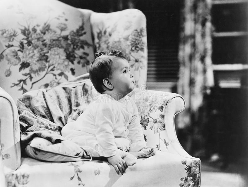 Baby sitting on armchair. (All persons depicted are no longer living and no estate exists. Supplier grants that there will be no model release issues stock images