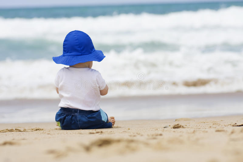 Baby sitting on beach. Rear view. Baby girl in a blue cap sitting on the beach looking at the ocean stock image