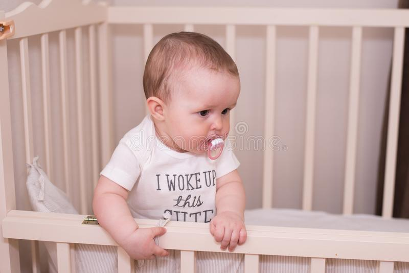 The baby is sitting on the bed and sucks the nipple stock images