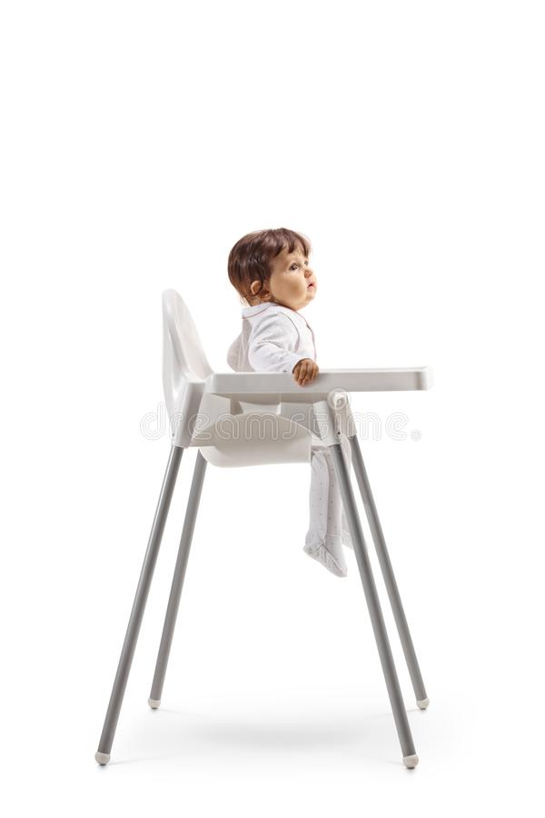 Baby sitting in a baby chair. Full length profile shot of a baby sitting in a baby chair isolated on white background royalty free stock photography