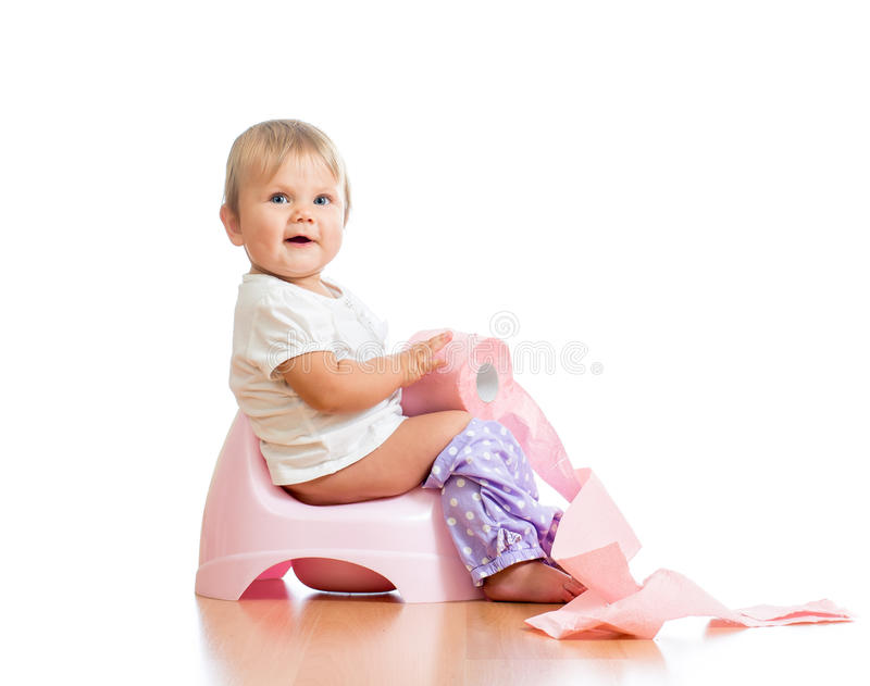 Baby sitting on chamber pot with toilet paper. Smiling baby sitting on chamber pot with toilet paper roll stock photography