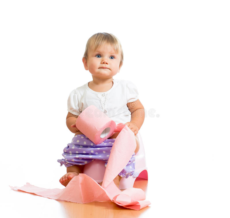 Baby sitting on chamber pot with toilet paper. Funny baby sitting on chamber pot with toilet paper roll royalty free stock photo