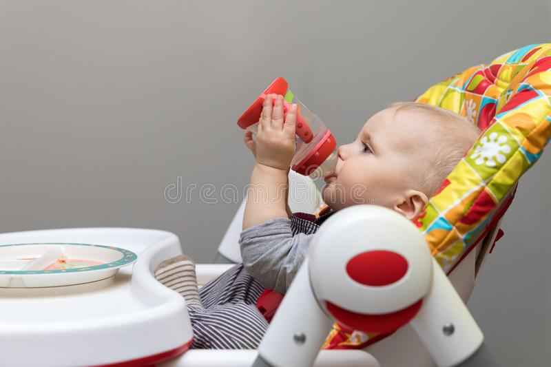 baby sitting in feeding chair and drinking water from bottle stock images