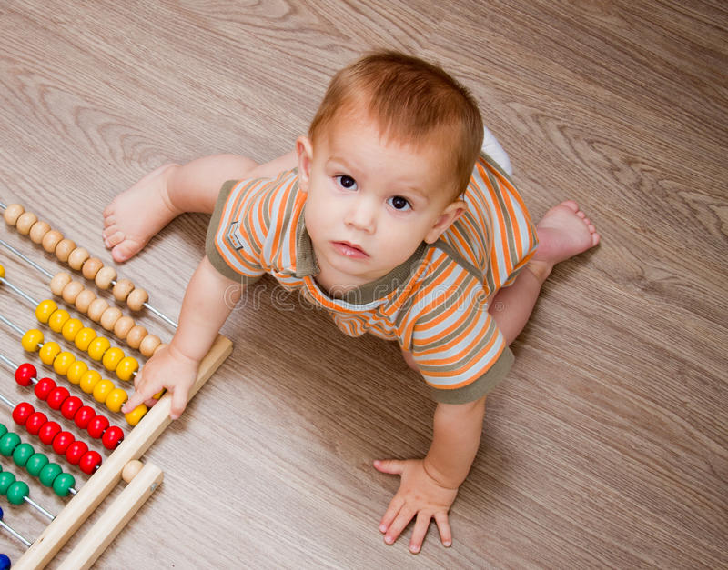 Baby sitting on the floor. With abacus stock images