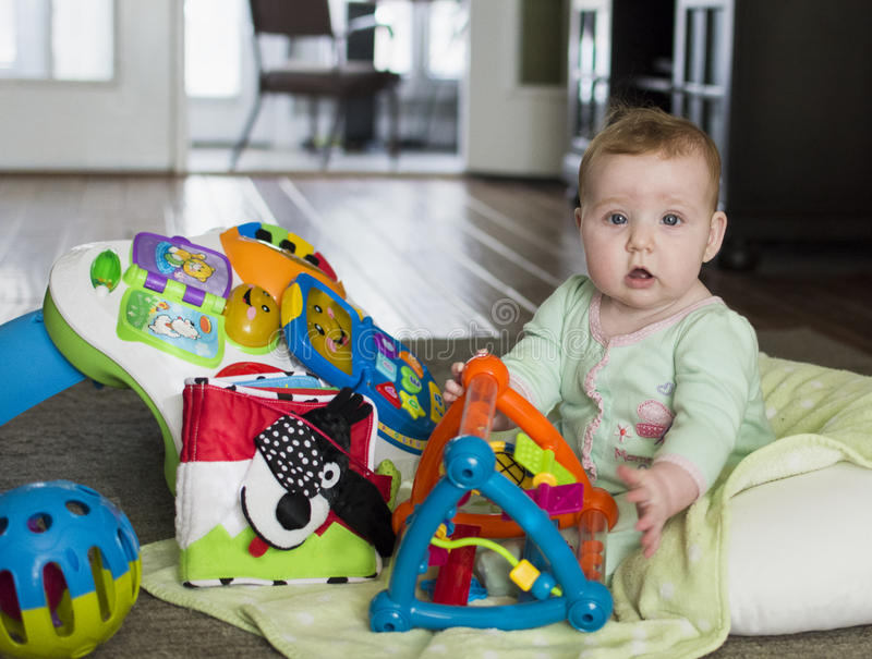 Baby sitting on floor with toys royalty free stock photography