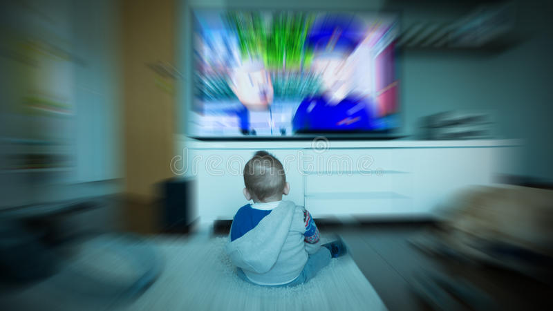 Baby sitting in front of TV stock photos