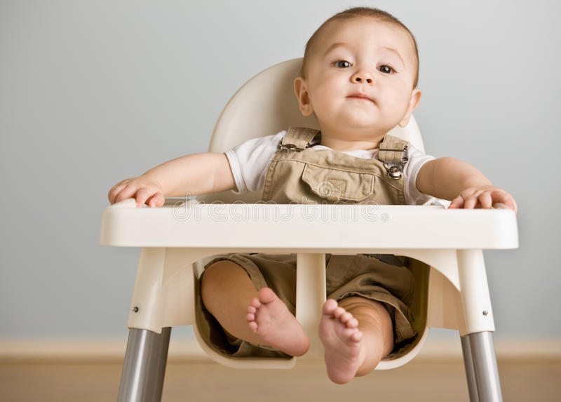 Baby sitting in highchair stock photo