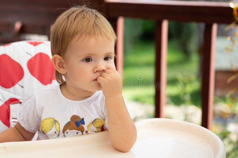 Baby sitting in highchair. Little girl siting at empty table and wait for your feeding royalty free stock photos