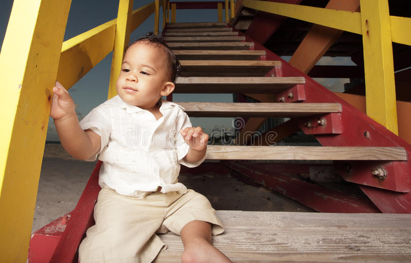 Baby sitting on a lifeguard stand. Adorable little baby sitting on a lifeguard hut at the beach stock photography