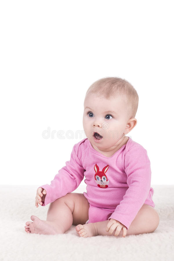 Baby sitting and looking surprised to the side royalty free stock image