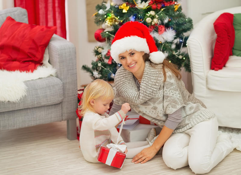Baby sitting near mother and open Christmas gift royalty free stock image