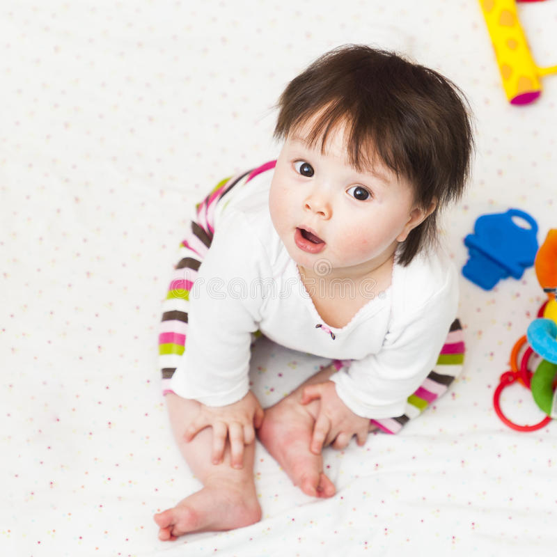 Baby sitting in playpen and looking up stock photo