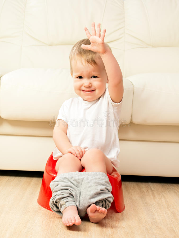 Baby sitting on potty in toilet. Baby sitting on the potty in the toilet royalty free stock image