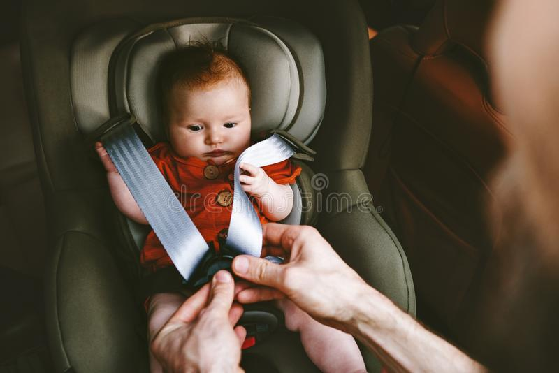 Baby sitting in safety car seat and father fastens belt stock photos