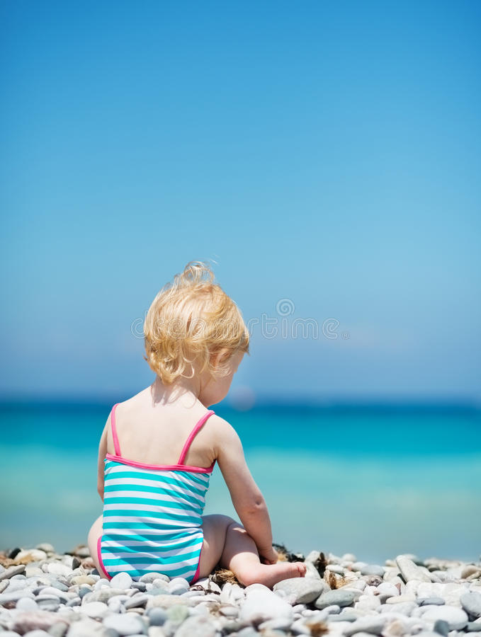 Baby Sitting On Sea Shore Stock Photos