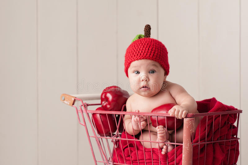Baby Sitting in a Shopping Cart Wearing an Apple Hat. A four month old baby girl wearing a crocheted, apple hat. She is sitting in a little, vintage shopping royalty free stock photo