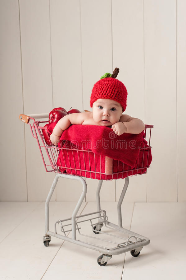 Baby Sitting in a Shopping Cart Wearing an Apple Hat. A four month old baby girl wearing a crocheted, apple hat. She is sitting in a little, vintage shopping royalty free stock image