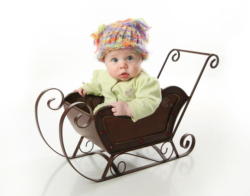 Baby sitting in a sled stock photo