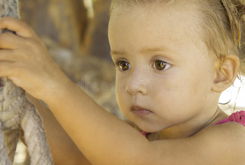 Baby sitting on swing and looking off into the distance. stock photos