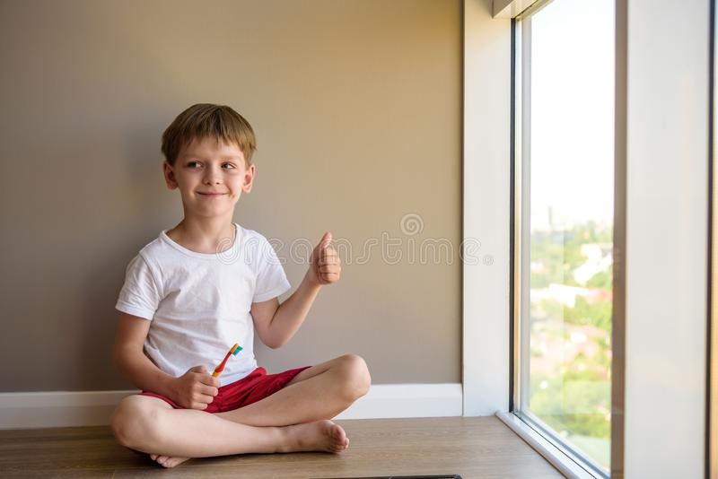 Baby sitting on a wooden floor of his house nibbling a toothbrush, while learning to brush his teeth stock photo