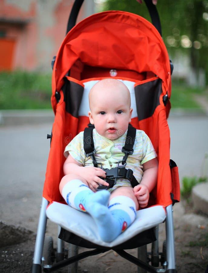 Baby in sitzendem Spaziergänger stockbild