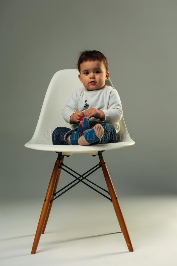 Baby sitzt auf dem Stuhl im Studio lizenzfreie stockfotos