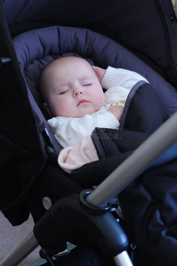 Baby in slaap kinderwagen stock afbeeldingen