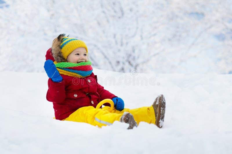 Baby on sled ride. Child sledding. Kid on sledge. Little boy enjoying a sleigh ride. Child sledding. Toddler kid riding a sledge. Children play outdoors in snow stock image