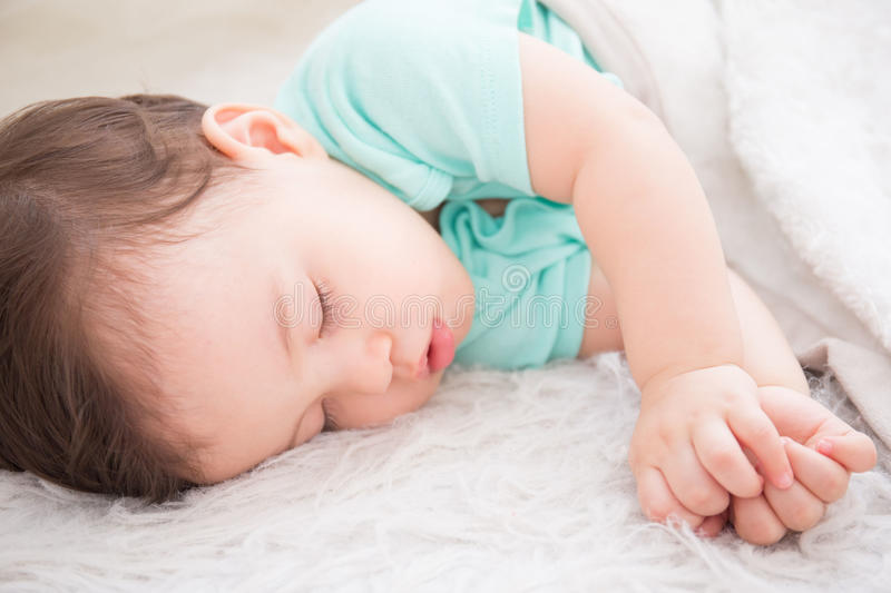 Baby sleep on the bed. Cute baby fist and sleep on the white bed in bedroom, caucasian stock photos
