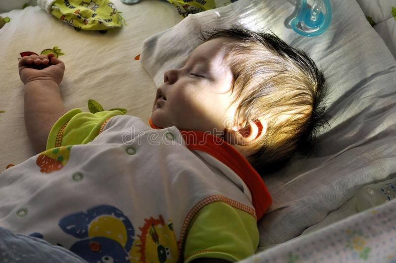Baby sleep in bed shined sun beam