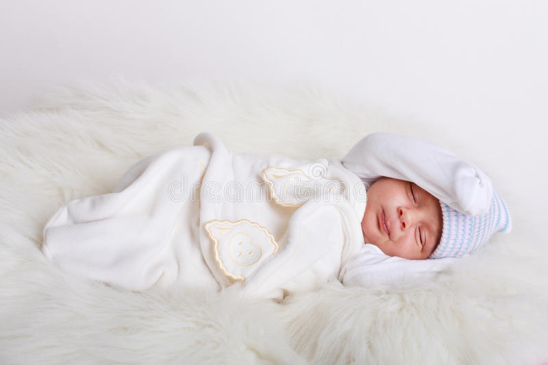 Baby sleeping. A 2 weeks old baby boy sleeping in a sheep skin royalty free stock photo