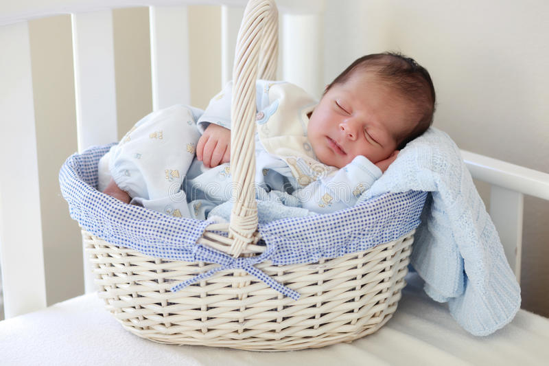 Baby sleeping. A 2 weeks old baby boy smiling while asleep in a basket royalty free stock photo