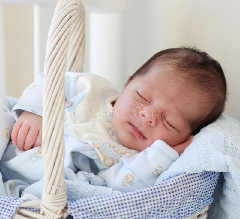 Baby sleeping. A 2 weeks old baby boy sleeping in a basket royalty free stock photography