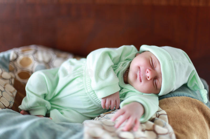 Baby sleeping. A 2 weeks old baby boy smiling while asleep on a bed royalty free stock photos