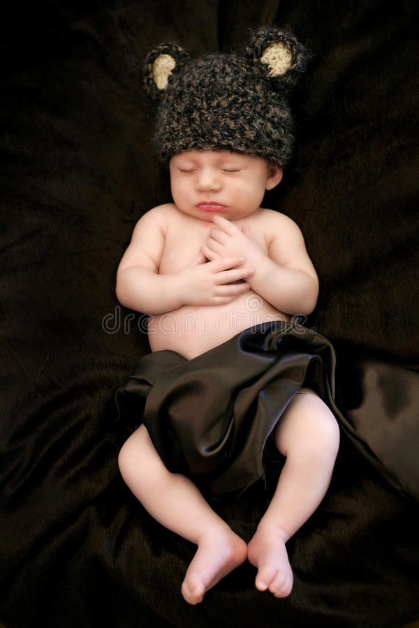 Baby sleeping. Newborn baby sleeping while wearing brown bear hat royalty free stock photo
