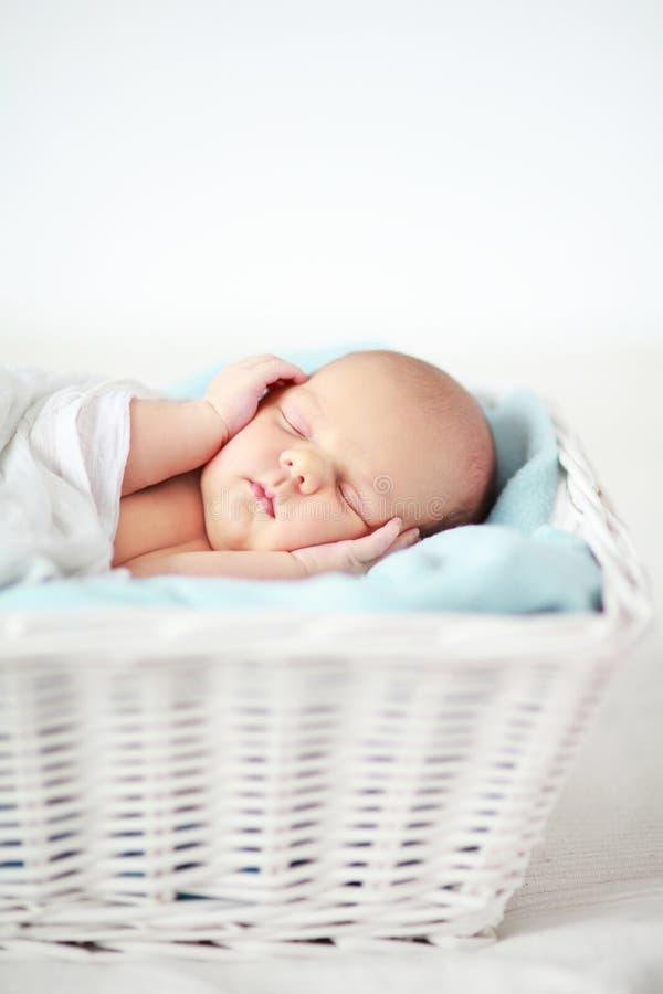 Baby sleeping in a basket. Adorable newborn baby girl sleeping stock photos