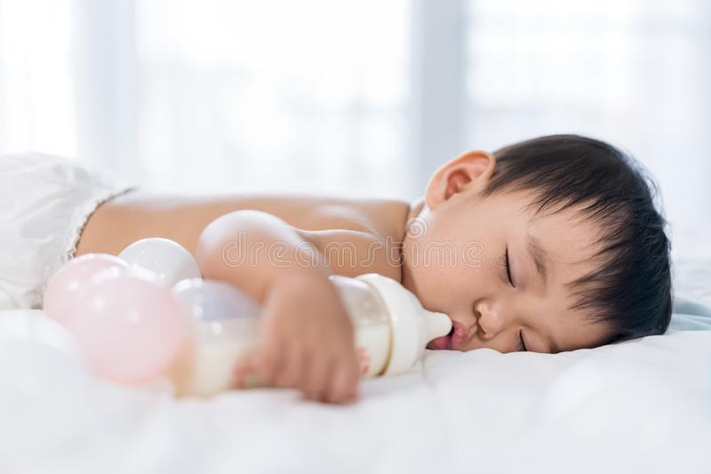 Baby sleeping on bed after drinking bottle milk stock photos