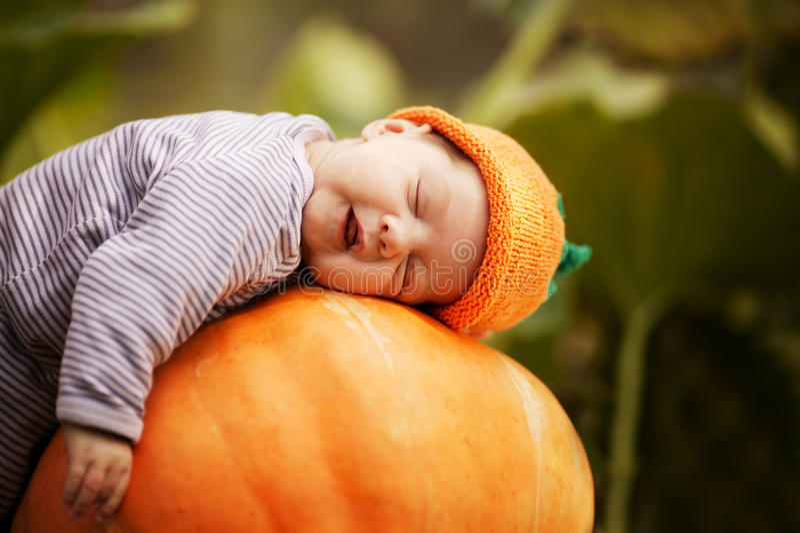 Baby sleeping on big pumpkin. Sweet baby with pumpkin hat sleeping on big orange pumpkin stock image