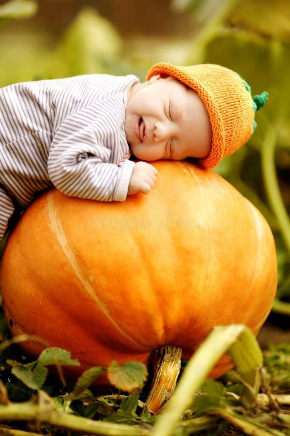 Baby sleeping on big pumpkin. Sweet baby with pumpkin hat sleeping on big orange pumpkin stock photography