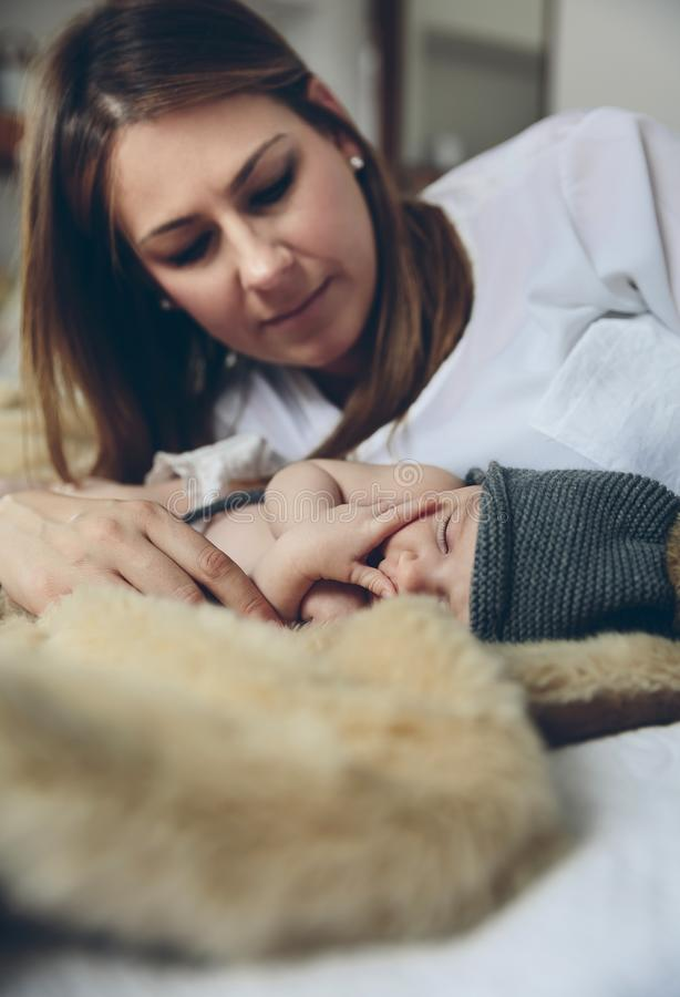 Baby sleeping on a blanket while her mother looks stock image