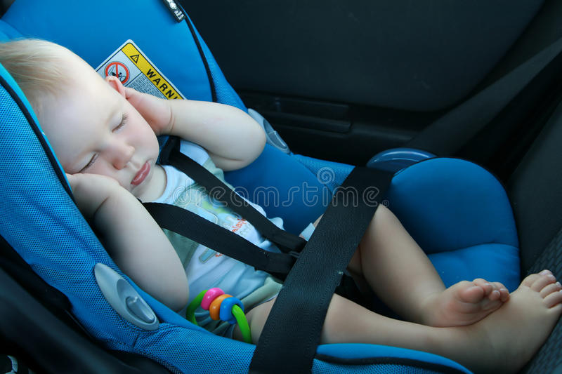 Baby sleeping in car seat. 9 months old baby boy sleeping in car seat stock photo