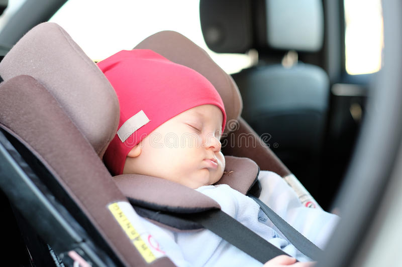 Baby sleeping in car seat. Five months old baby sleeping in car seat royalty free stock photography